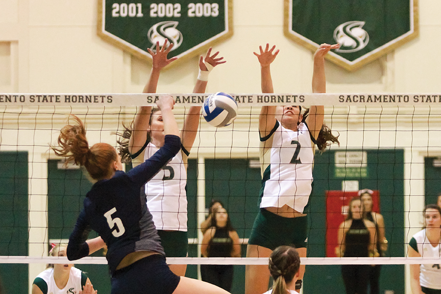 Sacramento State senior blockers Courtney Dietrich and Madeline Cannon block the ball from Lauren Jacobsen of Northern Arizona at Colberg Court on Oct. 27. (Photo by Matthew Dyer)
