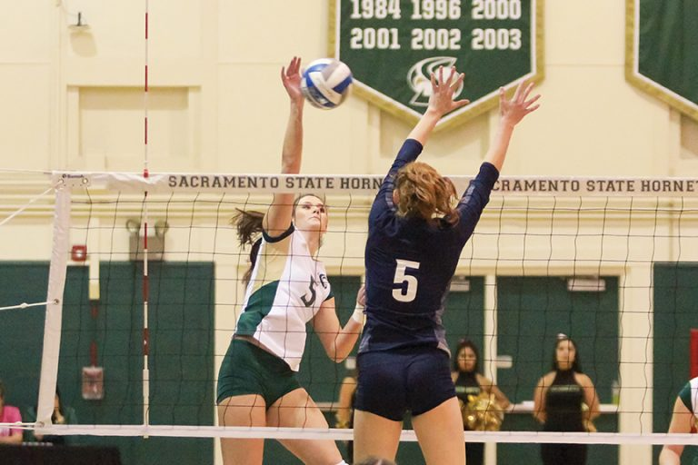 Sacramento State senior outside hitter Madeline Cannon spikes the ball past Lauren Jacobsen of Northern Arizona at the Hornets Nest on Oct. 27. (Photo by Matthew Dyer)