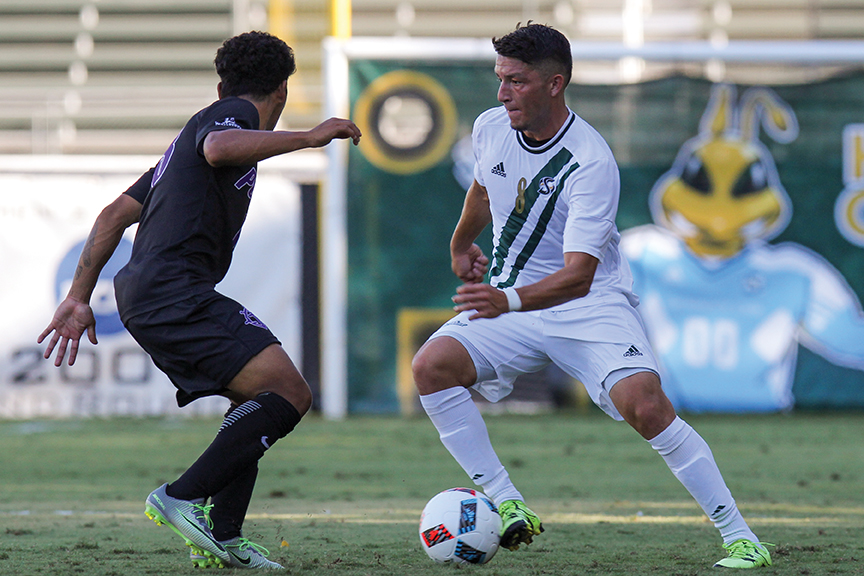Sacramento State senior midfielder Ivan Ramirez dribbles the ball past a Portland defender at Hornet Field on Sept. 15. (Photo by Matthew Dyer)