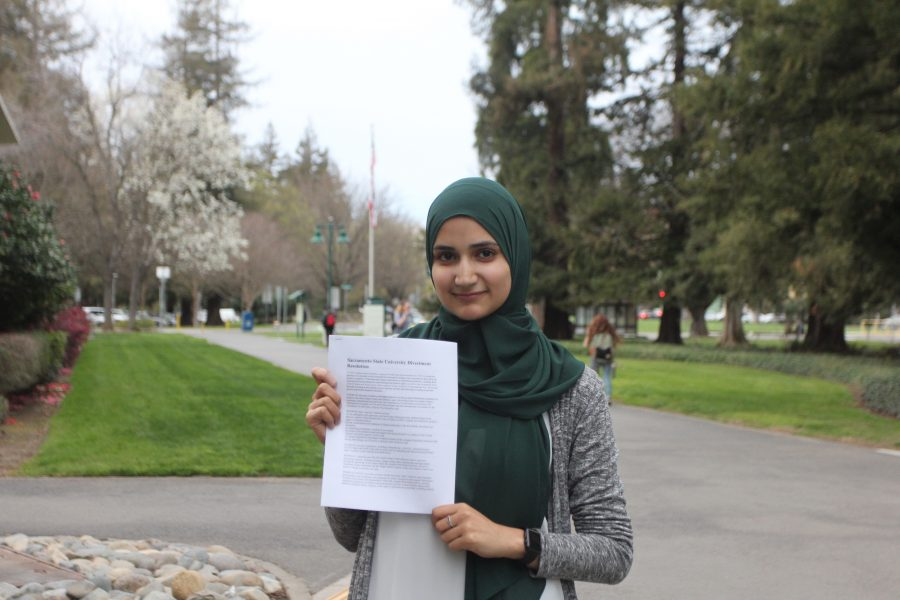 Aya+Khalifeh%2C+the+president+of+Students+for+Justice+in+Palestine%2C+holds+a+copy+of+SJP%27s+divestment+resolution%2C+which+calls+for+the+CSU+to+let+contracts+with+certain+corporations+expire.+%28Photo+by+John+Ferrannini%29