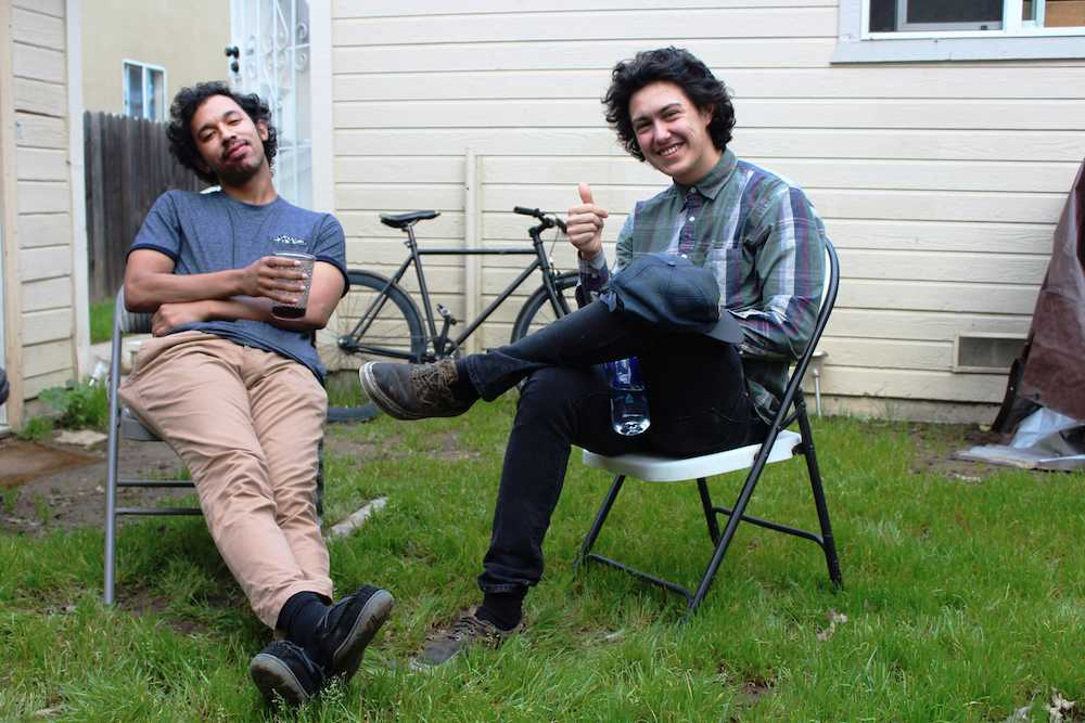 Derek Lynch, left, and Frank Lopes Jr., better known as Hobo Johnson and the Lovemakers, relax in the Oak Park backyard where they produce their music. (Photo by Claire Morgan)