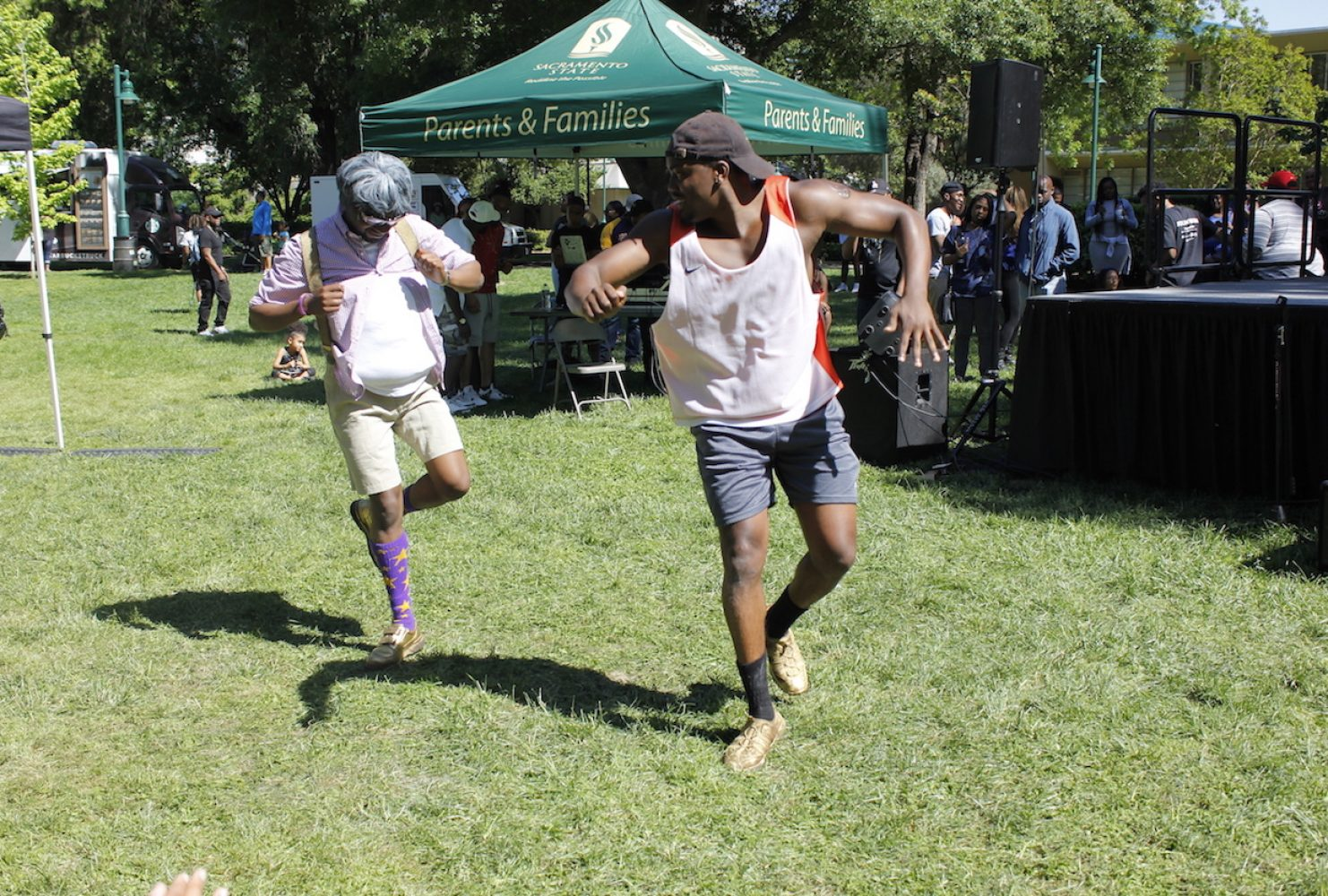 """Fraternity Omega Psi Phi members Moises Seraphin, left, dance along to live music during Black Family Day on April 29 in the Main Quad. Seraphin said that the event was """"an opportunity for organizations to connect and show support and for members to get involved around campus."""" (Photo by Rin Carbin)"""