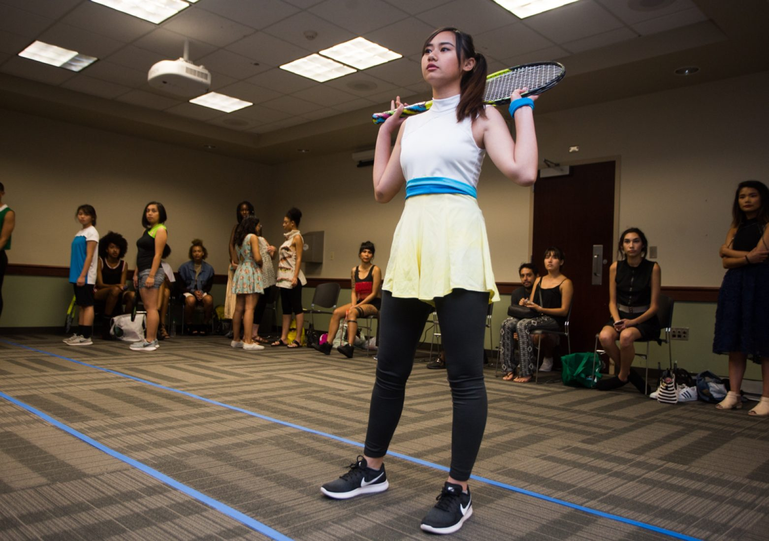 A model practices her runway walk in a Phua Lee design during rehearsal in the University Union Foothill Suite on Wednesday. Many of Lee's models in her 'Take the Hint' collection carry tennis racquets on the catwalk. (Photo by Nicole Fowler)