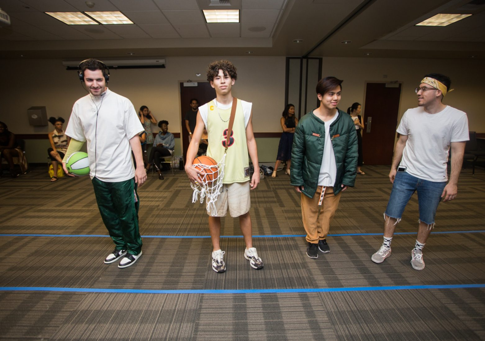 Menswear designer Jose Avila, far right, stands next to his models during rehearsal in the University Union Foothill Suite on Wednesday. (Photo by Nicole Fowler)