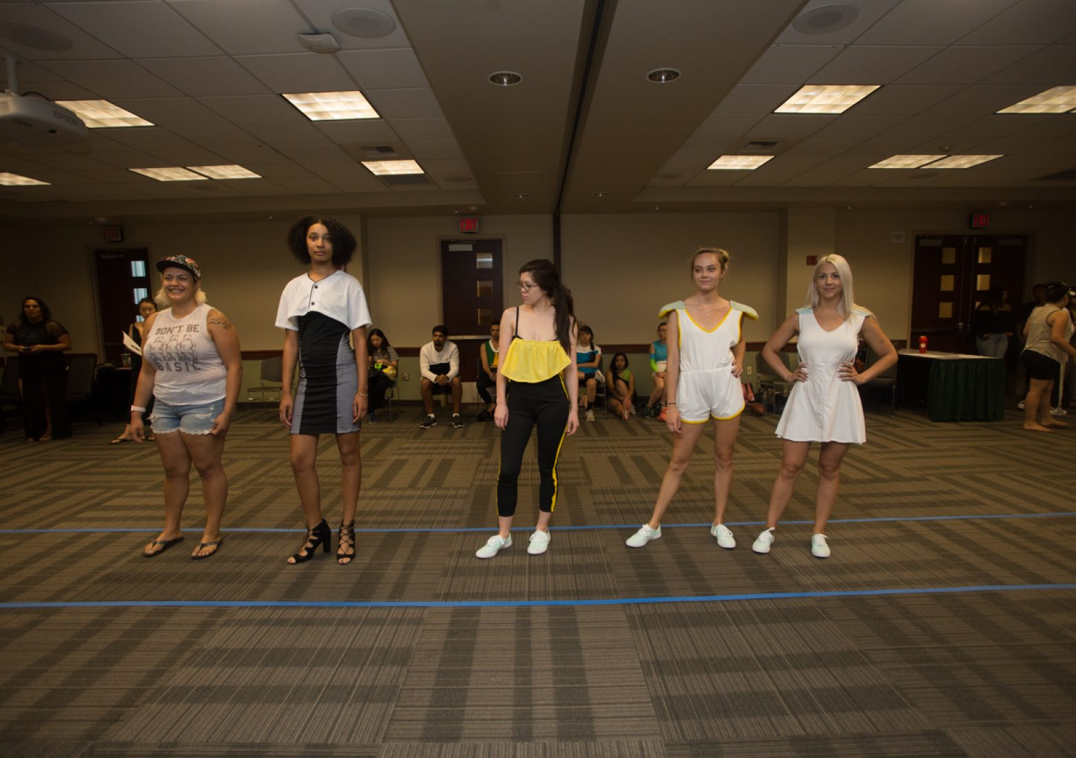 """Designer Alicia Tuatagaloa, far left, stands with three of her models who wear designs from her """"Touchback"""" collection during rehearsal in the University Union Foothill Suite on Wednesday. (Photo by Nicole Fowler)"""