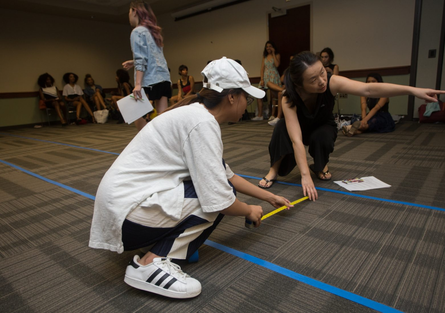 SFA faculty adviser Dong Shen and a volunteer measure the width of the mock runway to meets the 3 feet criteria during rehearsal in the University Union Foothill Suite on Wednesday. The catwalk at Golden 1 Center will change from a stage runway to a 3-foot-wide red carpet. (Photo by Nicole Fowler)