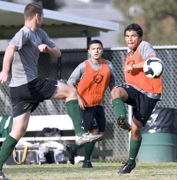 Defender Oscar Torrico sends the ball across the field in a scrimage during practice.: