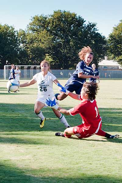 Women's Soccer vs. UCD 1:Hornets' forward Leah Larot and Aggies goalkeeper Kathleen Brandl go after the ball at the same time during a game against UC Davis on Friday at Hornet Soccer Field. The Hornets lost to the Aggies 1-0.:Robert Linggi - State Hornet