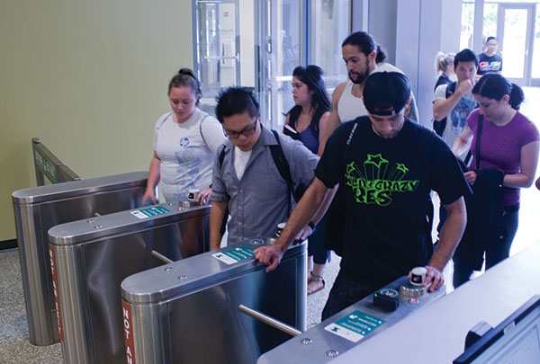 Finger scans at The Well :Sacramento State students use the finger-scanning turnstiles to enter The Well.:Rachel Lotz - State Hornet