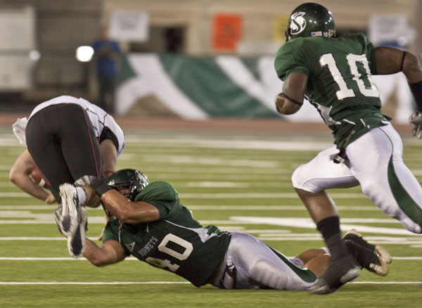 football1:Peter Buck (40) tackles the Western Oregon University's quarterback at Saturday night's football game in Hornet Stadium.:Julie Keefer - State Hornet