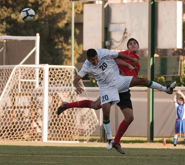 soccervsseattle:Jumping up for a header, Junior Erick Lariz, keeps ball away from Seattle player.:Rachel Lotz - State Hornet