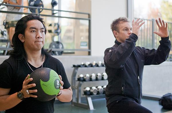 WELL personal trainers:Personal trainer Sam Brinkhuis, right, demonstrates medicine ball lifts with the help of a Well employee.:Robert Linggi - State Hornet