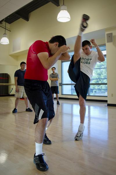 mma1:President Drew Verdi practices high kick combos with junior member Jesus Vega.:Steven Turner - State Hornet