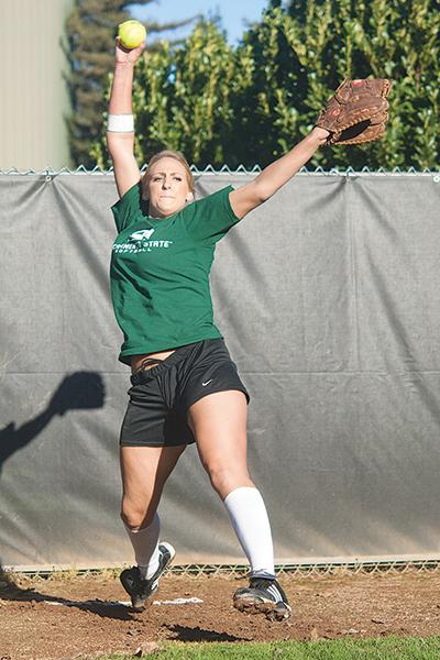 Softball 1:Top: Shelby Voelz, a junior pitcher, works on conditioning her arms and her reflexes for the upcoming softball season.:Jesse Charlton - State Hornet