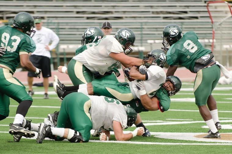 Junior+running+back+Sam+McCowan+gets+pulled+down+during+Saturday%E2%80%99s+green-gold+game.+The+defensive+team+clearly+held+the+upper+hand+during+the+game+keeping+the+offensive+to+one+touch+down+and+a+field+goal+while+forcing+four+turnovers.