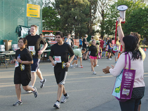 Spectators cheer for runners at the finish line of the Sac State 5K Fun Run on Thursday.
