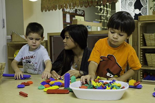 Brandt, in blue, and Tyler, in orange, play with building blocks as their student teacher, Caitlin, assists them.