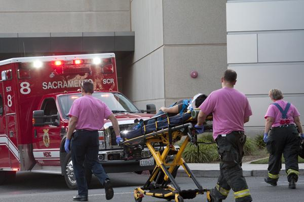 Paramedics wheel the victim to an ambulance. The woman was hit on her bike by a car behind the Hornet Bookstore.
