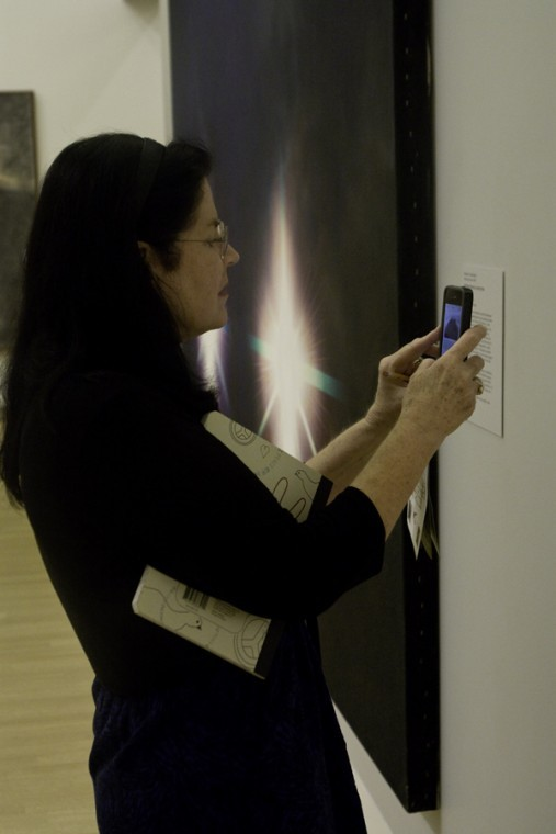 Susan Doherty, workshop participant, takes a photo of one of her favorite paintings at the Crocker Art Museum Thursday.