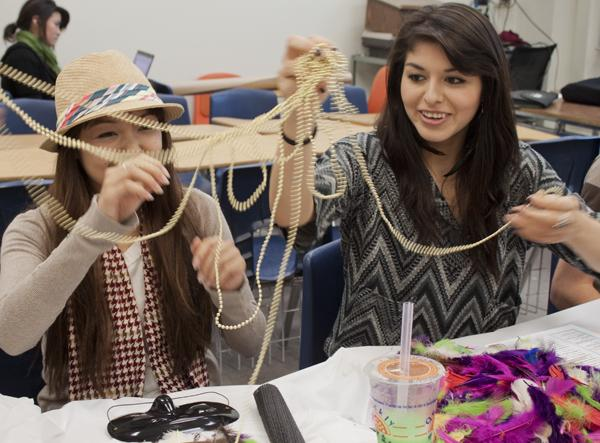 Nikki Khotpanya, senior apparel marketing and design major, and Anai Vivanco, sophomore business major, use beads to decorate their masks to sell at the upcoming fashion show.