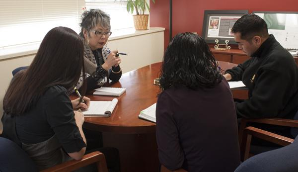 Carole Hayashino, vice president for University Advancement, is in a meeting to plan an event with commencement and special events; Coordinator Tess Simas, Mimi Phothichack and advancement assistant R. Paul Villaluz.