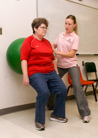 Julia Sheremet, a second year physical therapy graduate student, helps Annette Morehouse stretch after working on her walking endurance, during one of the Friday mock clinics in Solano Hall.