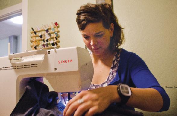 Hannah Hicks, designer for PLDM, works on a pair of women's jeans.