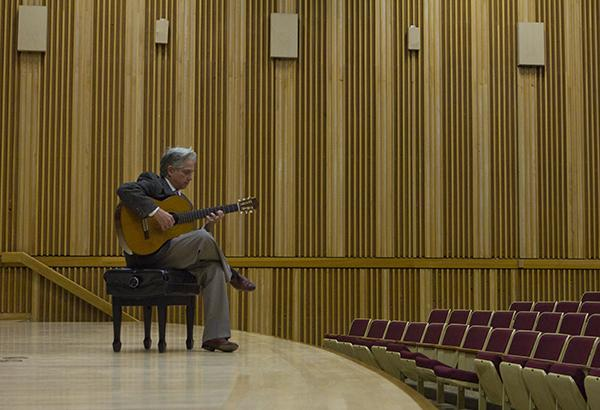Music professor and 2012 Grammy-nominated Richard Savino plays the guitar before instructing his History of Rock and Roll class.