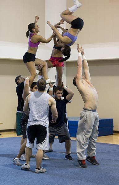 Men on the Sacramento State cheerleading team hold up the women after completing a stunt. The men are required to be in excellent shape to hoist up team members.