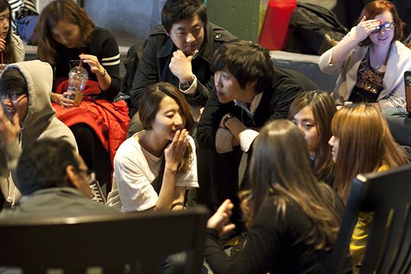 Students of the English Language Institute, a program teaching foreign students the mastery of the English language, huddle close together to hear everyone in their group of the roaring conversations of American culture on Thursday in the fireplace lounge.
