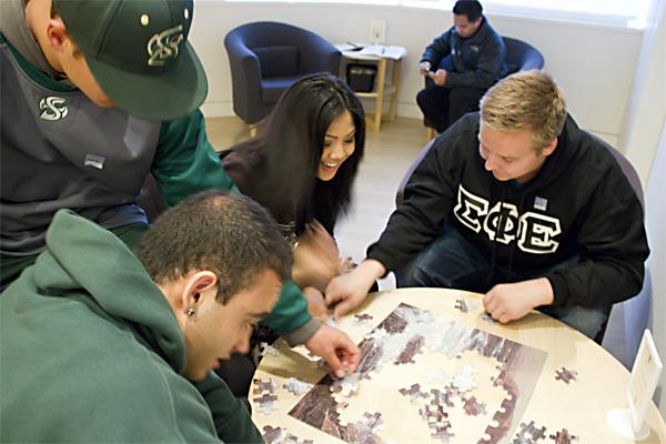 From left to right, Freshman business major Nasser Bseiso, undeclared freshman Chase Hunt, freshman psychology major Camille Paulos, and freshman biology major Tyler Jarrett enjoy a puzzle at the U-Nite event Thursday night located at the Crocker Art Museum.