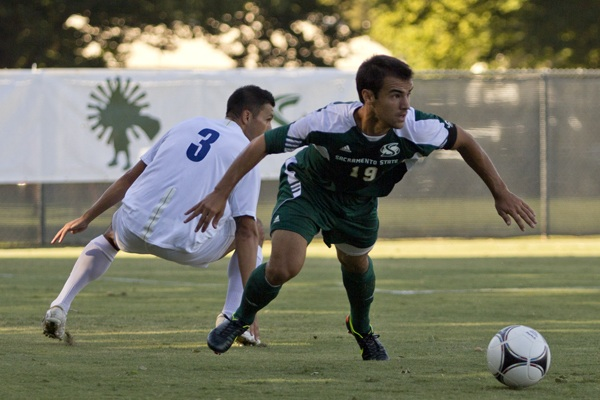 Sacramento State senior midfielder Alex Lopez tries to get away from San Diego's Matthew Chavez Friday at the Hornets' home opener. The game went into overtime and Sac State won 2-1.