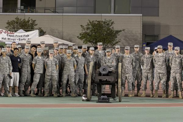 ROTC cadets pose behind the cannon.