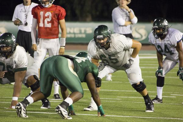 Sac State football offensive lineman No. 65, Vince Weaver, and Line Backer #44, Darnell Sankey, run mock drill at Wednesday night practice at Hornet Stadium.