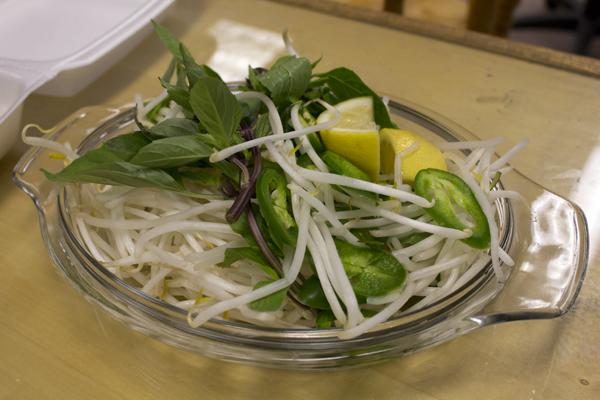 A plate of garnishes to add to the pho includes: lemon, jalapenos, bean sprouts, and mint leaves.