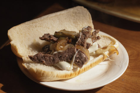The finished Philly cheese steak sandwich is plated and ready to eat.