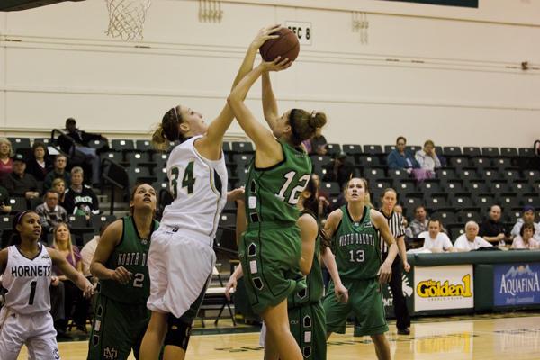 Hornet senior forward No. 34 Megan Kritscher attempts to block a shot against North Dakota on Thursday in the Nest.