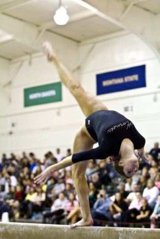 Kalliah McCartney performs a front aerial during her beam routine during a meet inside The Nest.