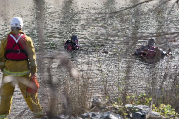 Divers extract the body found in the American River on Tuesday morning. Scott Morse, spokesperson for the Sacramento City Police, said the body will be identified by the coroner's office.