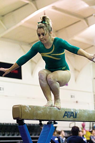 Dallas Smith regains her balance after performing a salto on the beam during the Sunday meet against the Air Force Falcons. Smith scored a 9.7 on the beam.