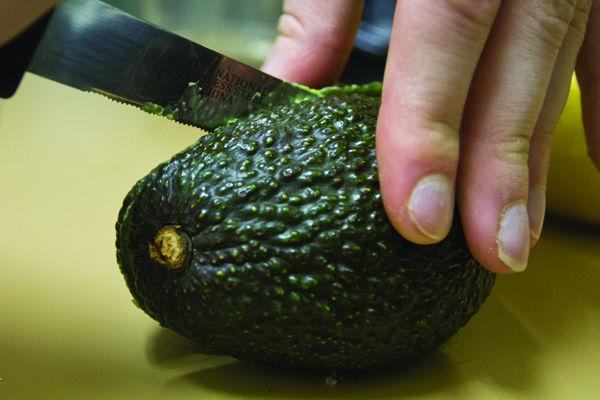 Slice one medium avocado in half to remove the pit.