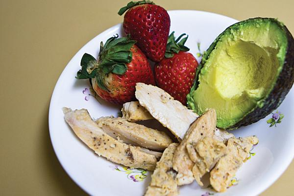 The main ingredients in this Paleo sandwich are chicken, strawberries, avocado, spinach and Paleo mayonnaise.