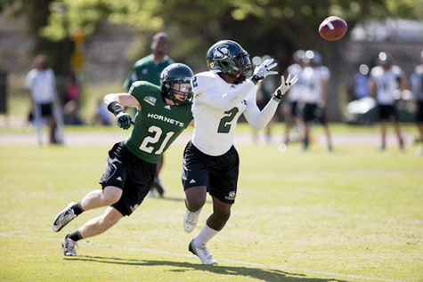 Hornet receiver No. 2, attempts to catch a pass while being defended by Hornet defensive back No. 21 at practice on April 11th at the Sac State practice field.