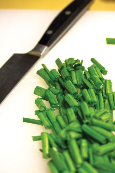Chop scallions before combining them with salt, pepper, olive oil and garlic powder.