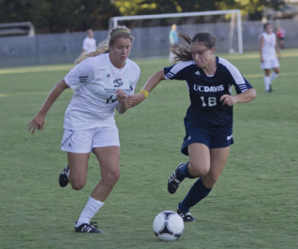 Sac State forward, No. 16, Kassidy Kellogg runs the ball past a UC Davis defender, but her effort was not enough for the Hornets on Friday.