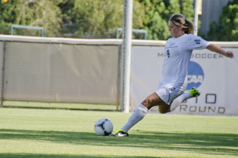 Sac State defender No. 8 McKenna Swanson conducts a corner kick during a game at Sac State.