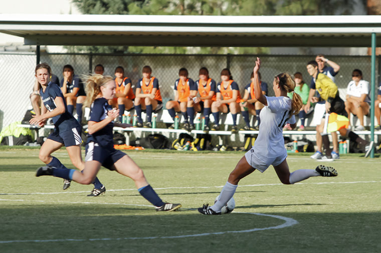 Sac State defender junior No. 12 Kassi Anast attempts to kick the ball passed her NAU opponent at the Oct. 11 game at Hornet Field.