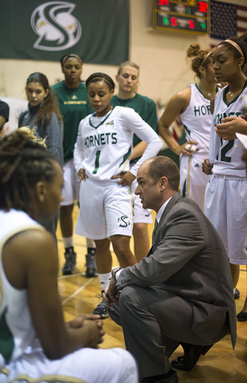 Women's basketball head coach Bunky Harkleroad talks to the team during a game inside The Nest.