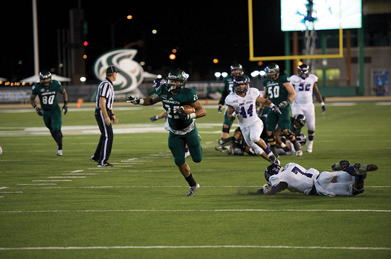 Sophomore running back Jordan Robinson rushes for a 30-yard touchdown run during the fourth quarter of the game against Weber State on Saturday.