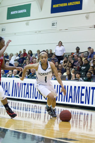 Senior Fantasia Hilliard dribbles past a Saint Mary's defender on Thursday, March 26, 2015 at the Hornets Nest. The Hornets were defeated 77-69.